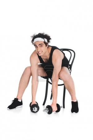 Skinny sportsman trying to raising dumbbells while sitting on chair isolated on white