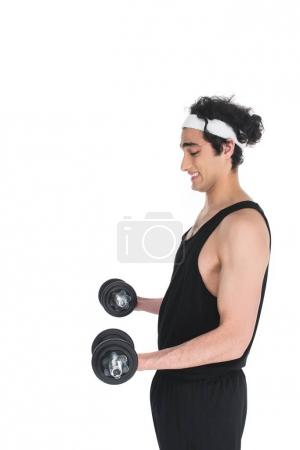 Side view of young skinny sportsman exercising with dumbbells isolated on white