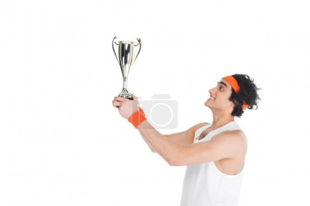 Side view of happy thin sportsman holding trophy isolated on white