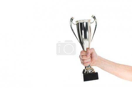 Close up view of silver trophy in hand of sportsman isolated on white