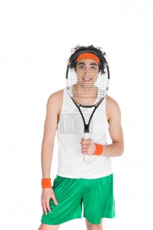 Young skinny sportsman looking through tennis racket isolated on white