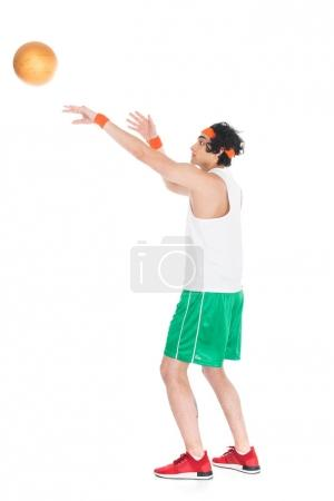 Side view of thin young basketball player throwing ball isolated on white