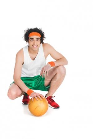 Smiling skinny basketball player sitting with ball isolated on white