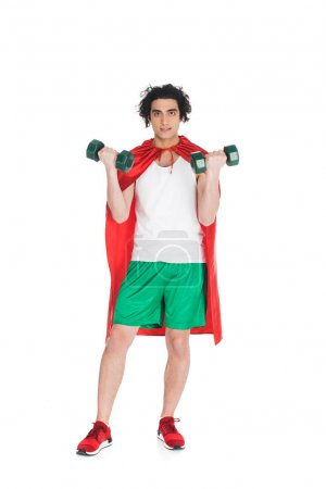 Thin sportsman with dumbbells in hands and wearing red cape isolated on white