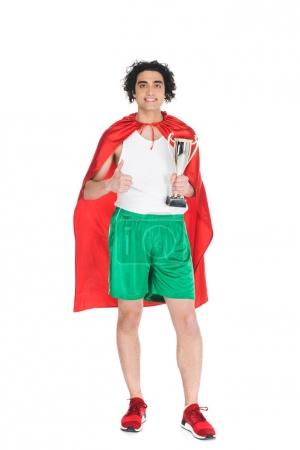 Thin sportsman with trophy in hands standing in red cape isolated on white