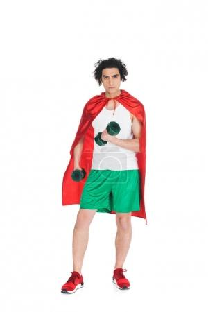 Thin sportsman with dumbbells in hands standing in red cape isolated on white