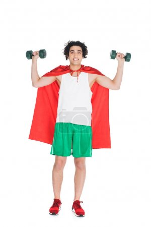 Smiling skinny sportsman with dumbbells standing in red cape isolated on white