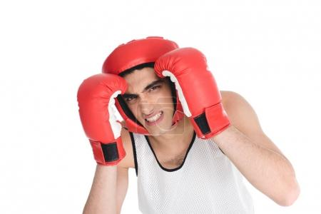 Skinny sportsman hiding face by hands in boxing gloves isolated on white