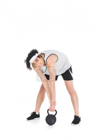 Young skinny sportsman raising kettlebell isolated on white