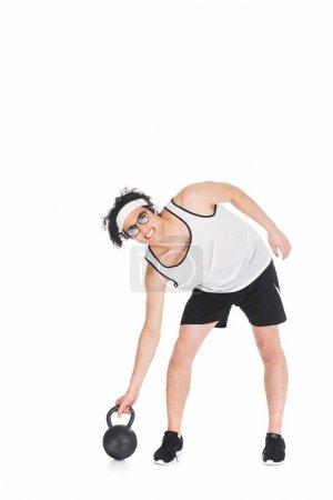 Thin sportsman in eyeglasses raising kettlebell isolated on white