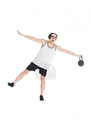 Young skinny sportsman in eyeglasses standing on one leg and holding kettlebell isolated on white