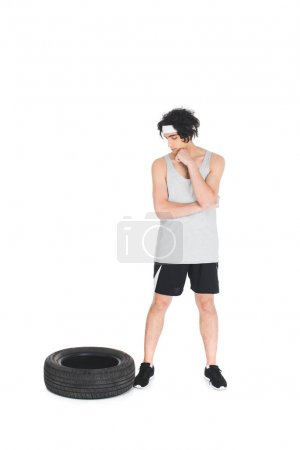 Skinny sportsman in headband looking at tire isolated on white