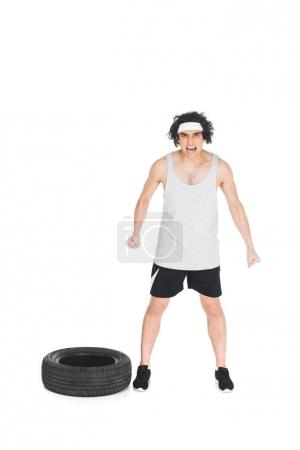 Angry skinny sportsman standing near tire isolated on white