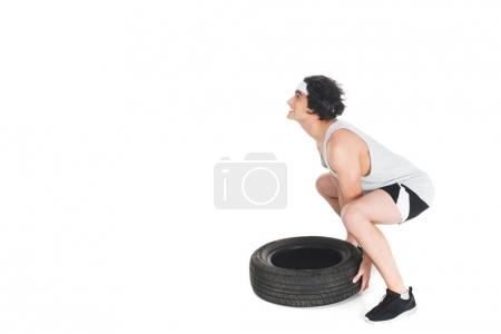 Side view of skinny sportsman raising tire isolated on white