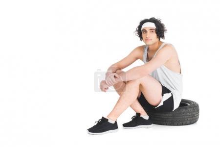 Photo pour Jeune sportif mince assis sur un pneu isolé sur blanc - image libre de droit