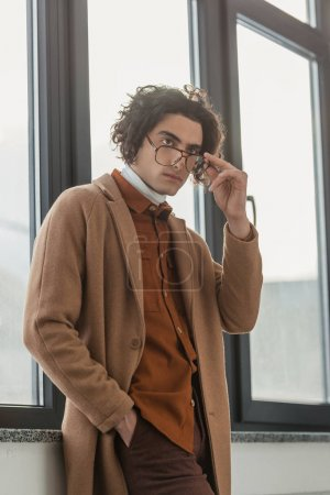 Young stylish man looking over eyeglasses