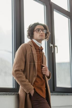 Low angle view of young stylish man in eyeglasses