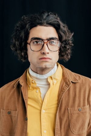 Portrait of male fashion model with curly hair in eyeglasses isolated on black