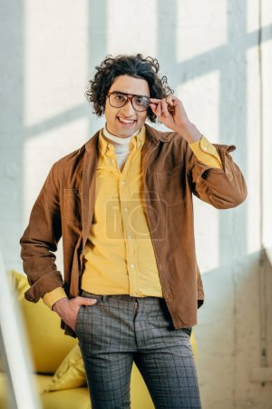 Smiling male fashion model holding eyeglasses