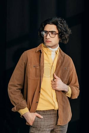 Young male fashion model in eyeglasses isolated on black