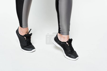 Photo for Close-up view of female legs in sports shoes isolated on white - Royalty Free Image