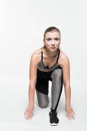 Sportswoman preparing to run isolated on white