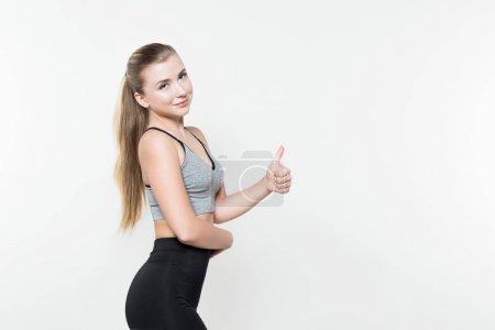 Photo for Sportswoman showing thumb up isolated on white - Royalty Free Image