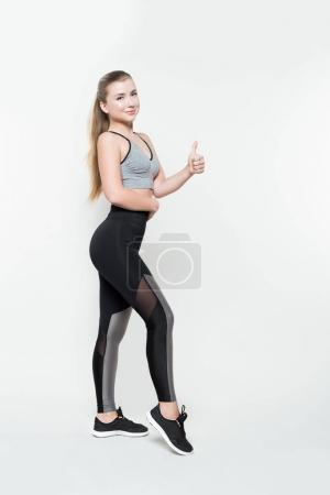 Photo for Attractive woman in sports clothes showing thumb up isolated on white - Royalty Free Image