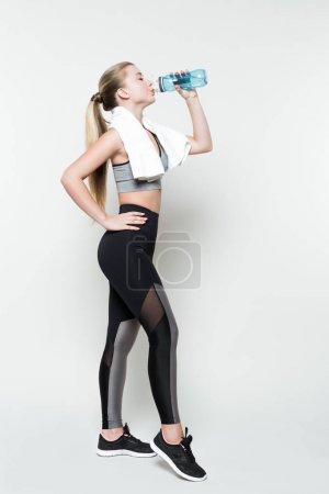 Photo pour Femme blonde en vêtements de sport avec serviette sur les épaules boire de la bouteille d'eau isolé sur blanc - image libre de droit