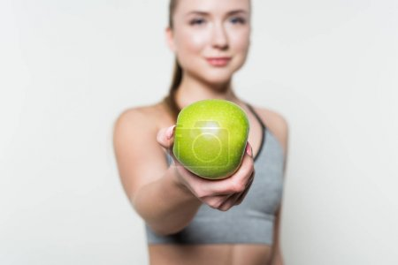 Apple in hand of fitness girl isolated in white
