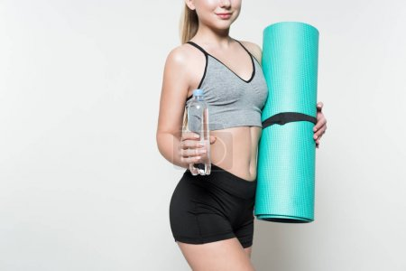 Attractive sportive woman holding water bottle and yoga mat isolated on white