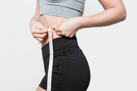 Close-up view of sportswoman measuring waist isolated on white
