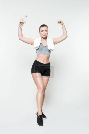 Athletic girl with water bottle and towel showing muscles isolated on white