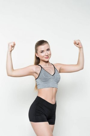 Fit girl showing muscles isolated on white