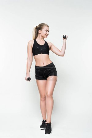 Athletic girl lifting dumbbells isolated on white