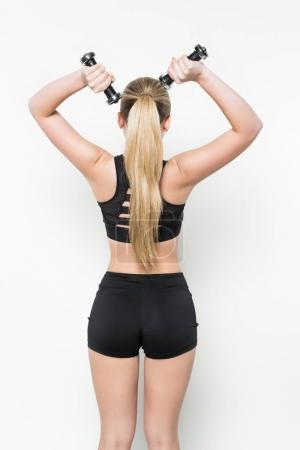 Rear view of woman in sports clothes with dumbbells isolated on white