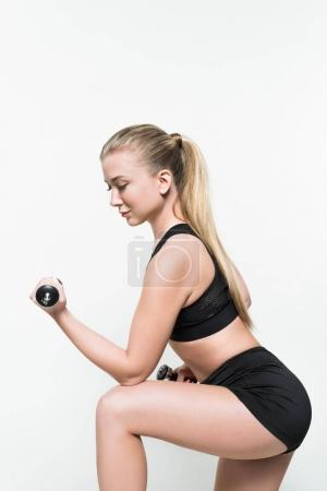 Young woman in sports top lifting dumbbell isolated on white