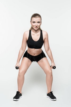 Fitness woman performing squat with dumbbells isolated on white