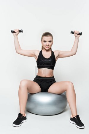 Fit girl with dumbbells on fitness ball isolated on white