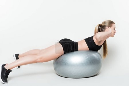 Fitness woman working out on fitness ball isolated on white