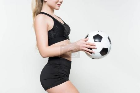 Young sportswoman in sports top playing with football ball isolated on white