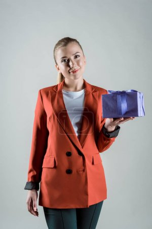 Photo for Smiling woman holding gift box isolated on grey - Royalty Free Image