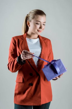 Happy woman opening gift box isolated on grey