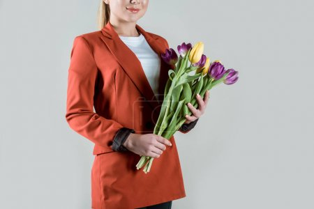 Close-up view of woman holding bouquet of tulips isolated on grey