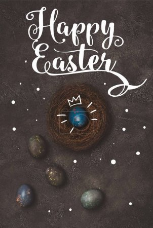 top view of blue easter egg with crown in nest on concrete table with Happy Easter lettering