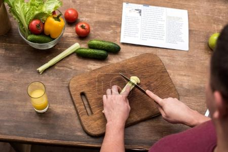 cropped shot of young man cutting celery on wooden chopping board