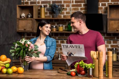 smiling young man holding travel newspaper and looking at happy pregnant wife arranging flowers in vase