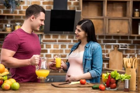 happy young pregnant couple holding glass and jug of fresh orange juice and smiling each other at kitchen