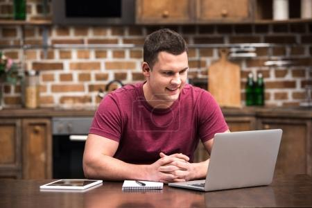 smiling young man using digital devices while working at home