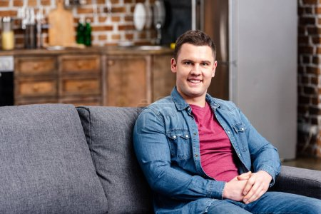 handsome young man sitting on couch and smiling at camera